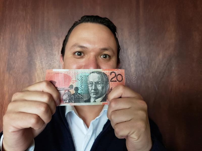 Young man showing and holding an Australian banknote of twenty dollars. Commerce, exchange, trade, trading, value, buy, sell, profit, price, rate, cash stock photo