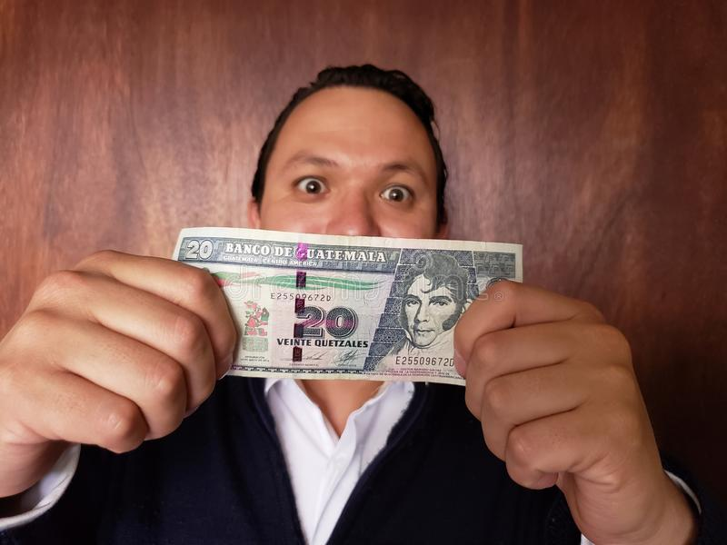 young man showing and holding a guatemalan banknote of twenty quetzales royalty free stock photos