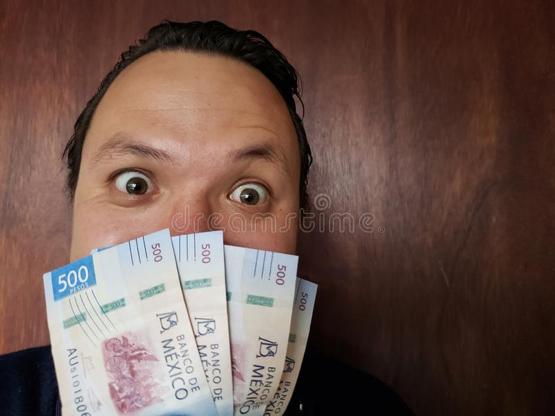 young man showing and holding a mexican banknotes of 500 pesos stock images