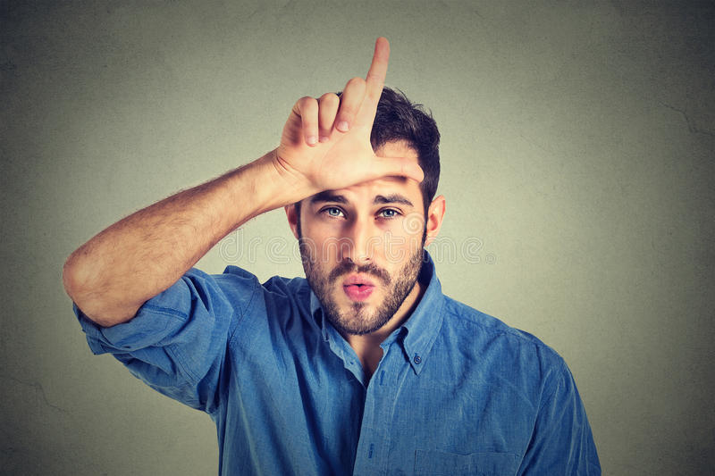 Young man showing loser sign on forehead, looking at you with disgust royalty free stock photo
