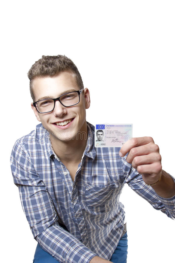 Young man showing off his driver license. Young man just recieved his drivers license and is happy to drive his own car soon royalty free stock photos