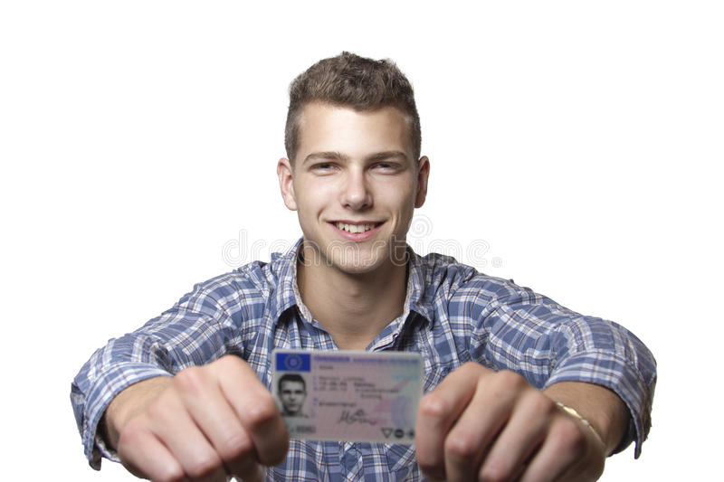 Young man showing off his driver license. Young man just recieved his drivers license and is happy to drive his own car soon royalty free stock image