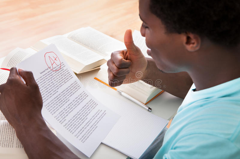 Young man showing a paper with grade a plus. Happy African Male Student Showing A Paper With Perfect Grade A Plus In Classroom stock photos