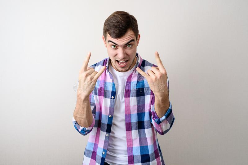 Young man showing rock sign with fingers on grey background stock photography