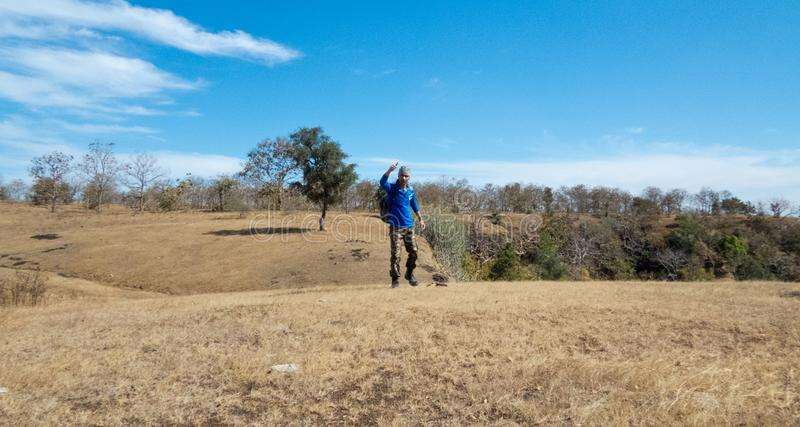 Young man showing thumps up after reaching hill/mountain`s peak successfully. A Young man in blue t-shirt and camouflage track pants showing thumps up after royalty free stock photos