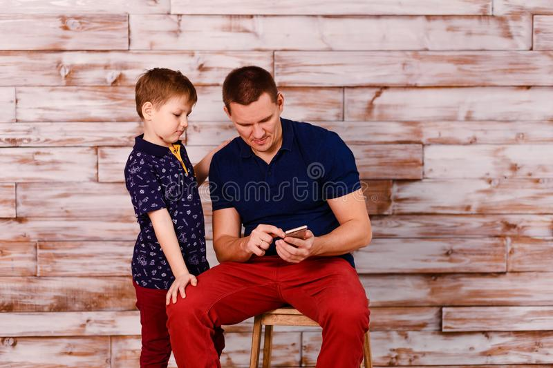 A young man shows his son a photo on a smartphone. Happy father and son with smartphone on wooden background royalty free stock photography