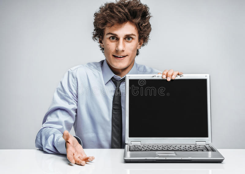Young man shows presentation on laptop. royalty free stock photo