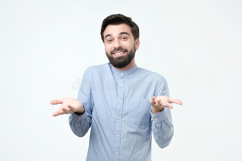Young man shrugging shoulders saying who cares so what I do not know gesture. Ignorance and arrogance. Young man shrugging shoulders saying who cares so what I royalty free stock image