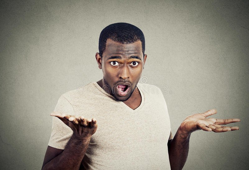 Young man shrugging shoulders who cares so what I don't know gesture stock photo