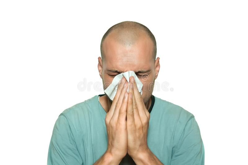 Young man sick from common cold flu blowing his nose with paper tissue isolated on white background. royalty free stock photos