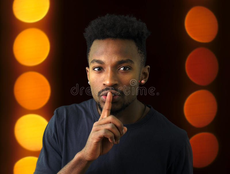 Young man silence expression shut up finger on mouth. Shut up silence finger on lips no talk expression dark scene stock images