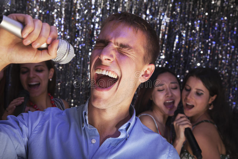 Young man singing into a microphone at karaoke, friends singing in the background. Young men singing into a microphone at karaoke, friends singing in the stock photography