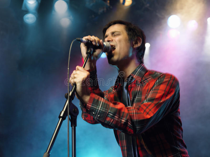 Young Man Singing Into Microphone. Low angle view of a young man singing into microphone on stage royalty free stock photo