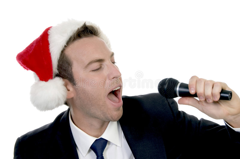 Young man singing into microphone with santa cap royalty free stock image