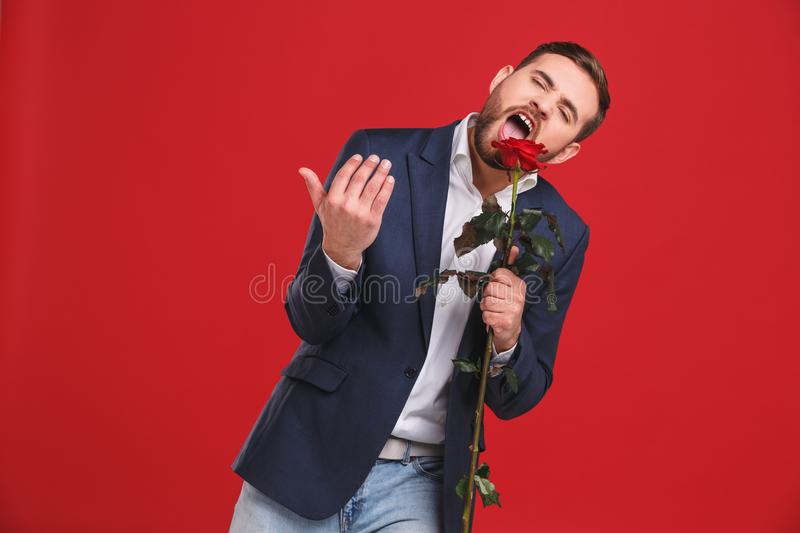 Young man singing into red rose stock photo