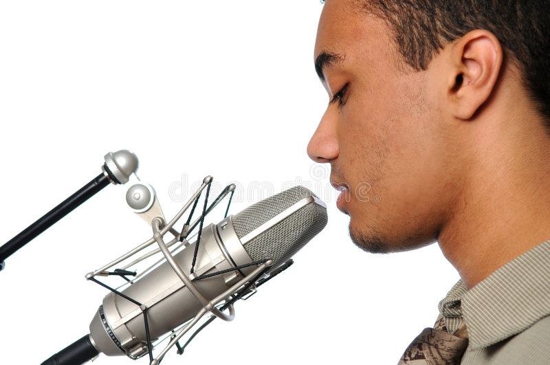 Young Man Singing into Vintage Microphone. Young man singing into a vintage microphone royalty free stock images