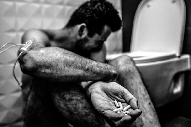 Young man sit on floor alone in rest room and taking drugs. He show handful of baddiction pills. Guy suffer and crying royalty free stock images