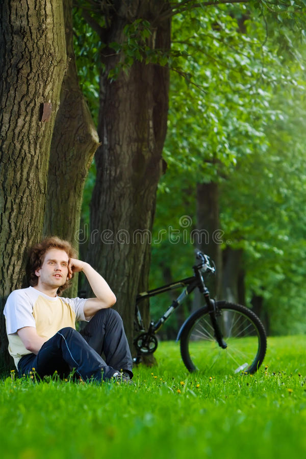 Free Young Man Siting Under The Tree Near His Bycicle Royalty Free Stock Images - 18258299