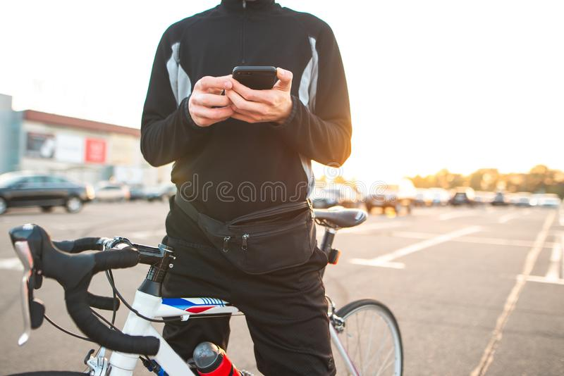 Young man sits on a bike and writes a message on the smarthophone stock photography