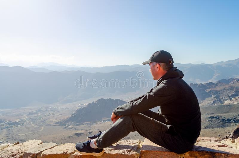 A young man sits on the edge of a cliff and looks at the valley and mountains of Egypt stock photos
