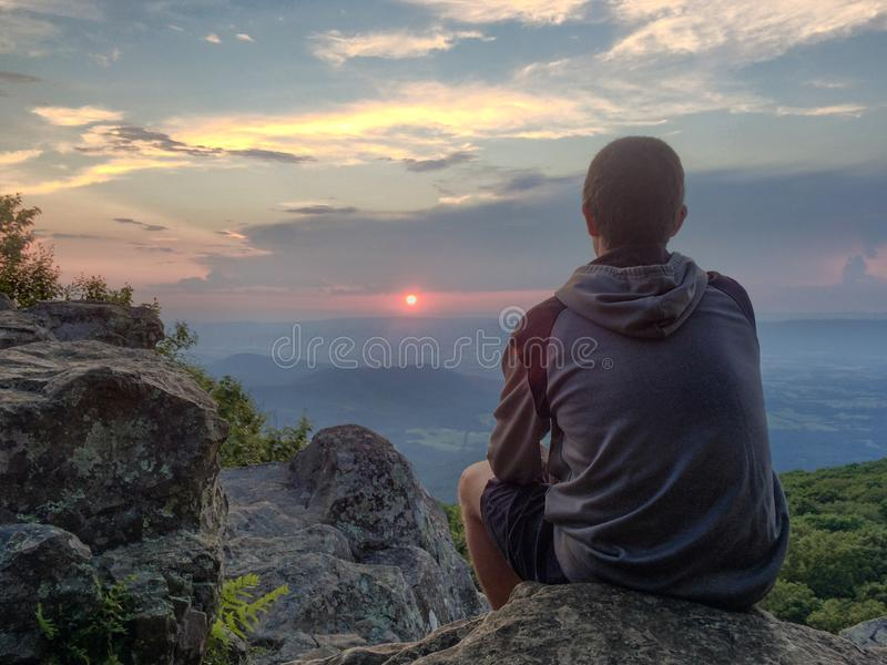 Young man watching sunset from mountain top in Shenandoah National Park. stock photo