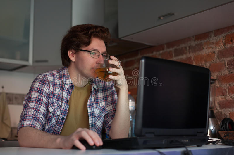The young man sits at a laptop in the kitchen and drinking tea. stock photo
