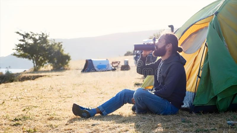 Young man sits on near the tent at campsite and drinking tea from thermos bottle. Young bearded hipster man sits on the ground next to touristic tent at stock image