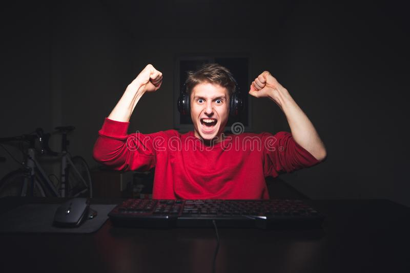 Young man sits at night, but uses a computer, rejoices with his hands raised. Happy Gamer is Joyful royalty free stock photo