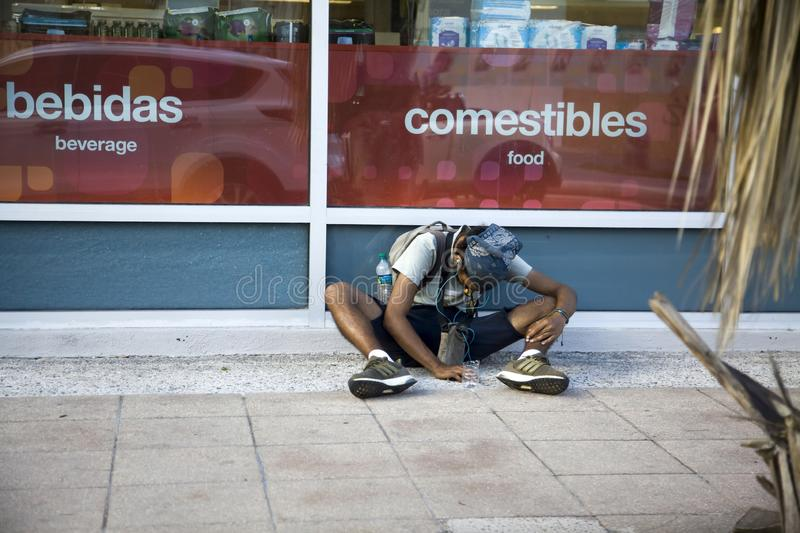Young man sits outdoors begging in Bayamon Puerto Rico. BAYAMON, PUERTO RICO/USA - February 10, 2019: Young man sits outdoors and begs for money royalty free stock photos