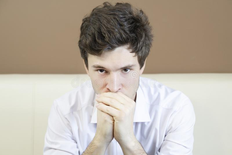 Man sits thoughtfully with folded hands. royalty free stock image
