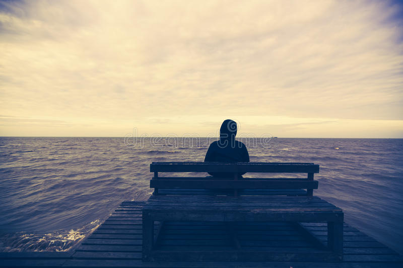 The young man sits on a wooden chair in the sea stock image