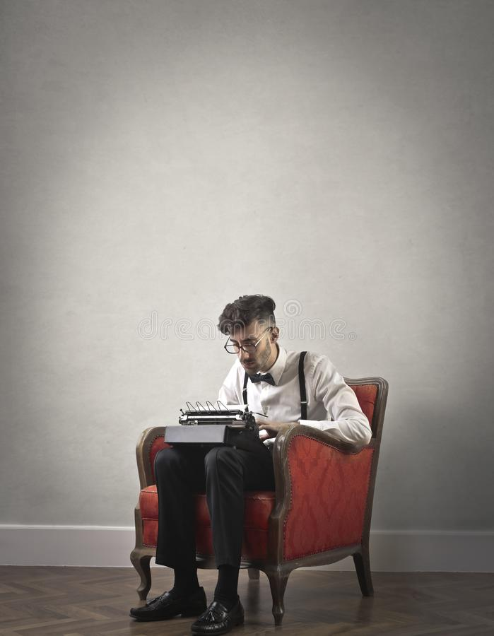 Young man using a typewriter. Young man sitting on an armchair and using a typewriter stock photos