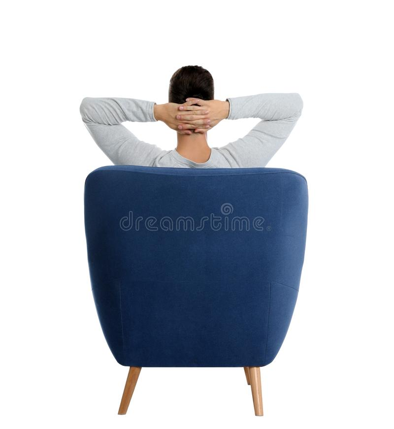 Young man sitting in armchair on background, view from back stock image