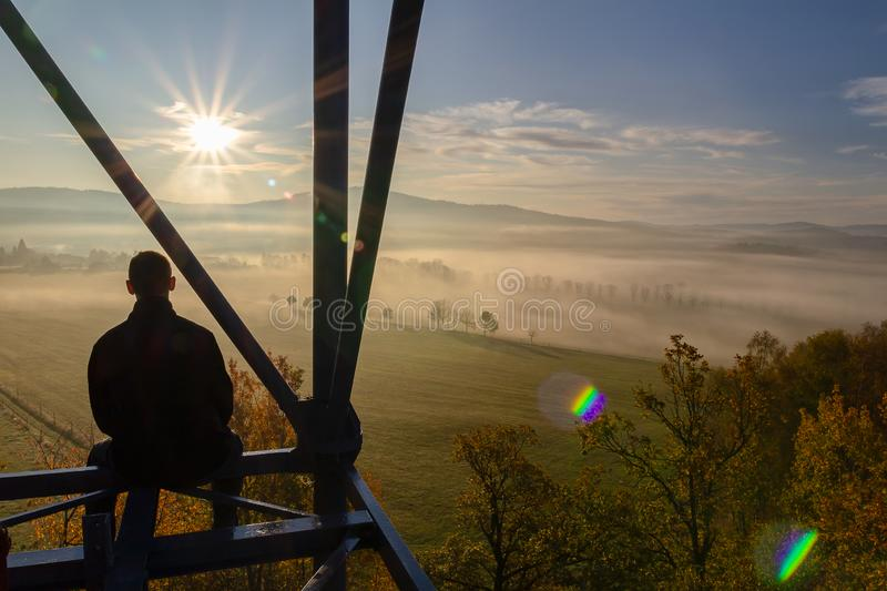 Young man sitting from back on watchtower construction looking to autumn foliage trees with misty fog and hill at sunrise, Czech stock photos