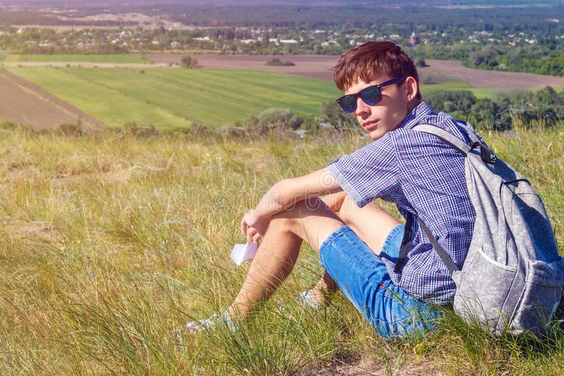 Young man sitting with backpack and looking at beautiful view, tourism concept stock photos