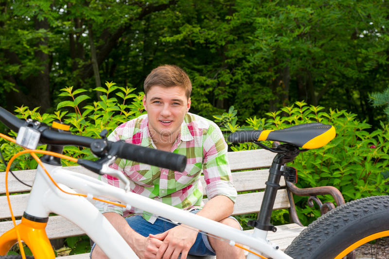 Young man sitting on bench near bike. With fat tires in beautiful green park royalty free stock photography