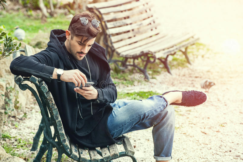 Young man sitting on the bench waiting with phone in hand stock photography