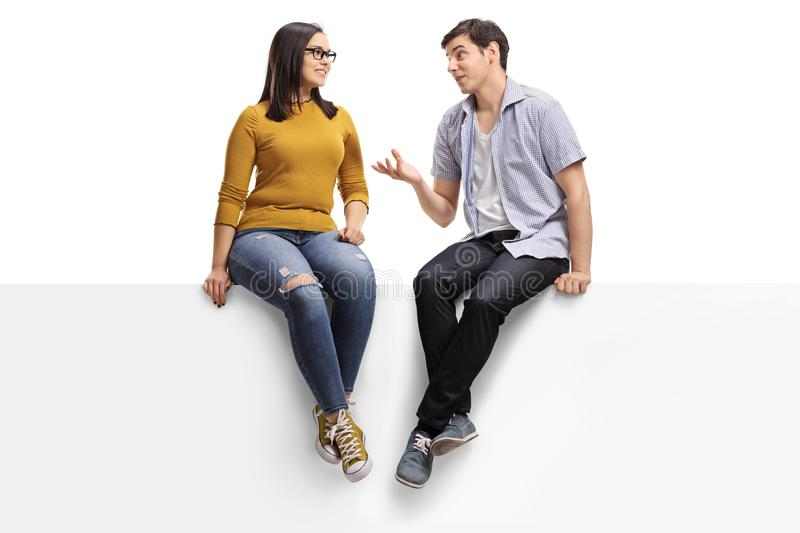 Young man sitting on a blank signboard and talking to a young woman royalty free stock photo