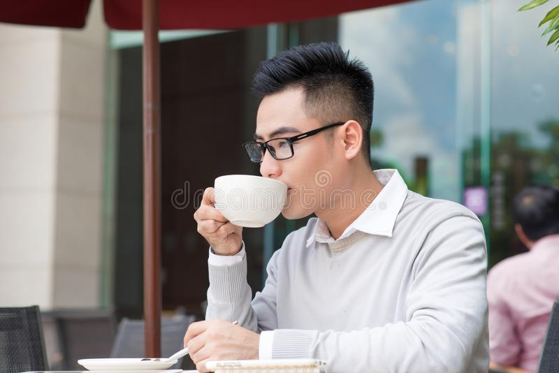 Young man sitting in a cafe on a coffee break. royalty free stock images