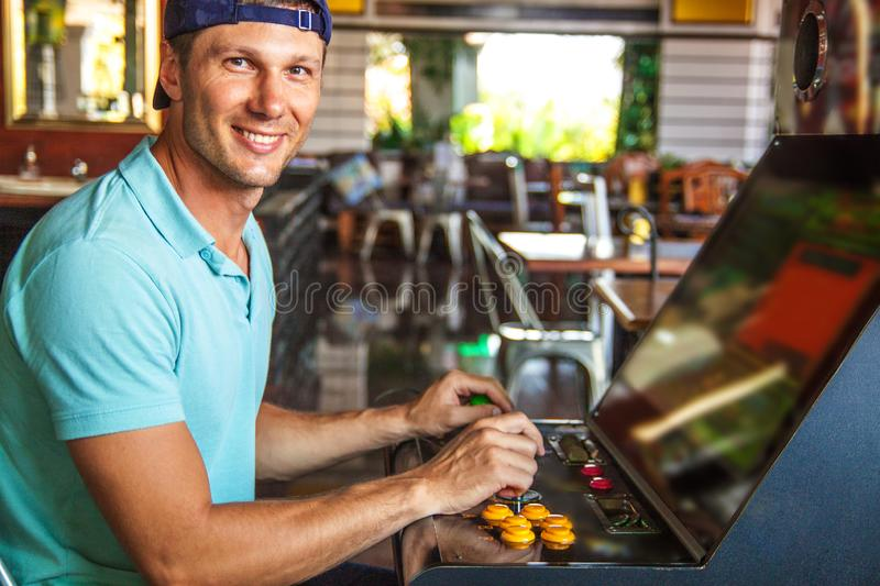 Young man sitting in casino and playing amusement machine. stock photo