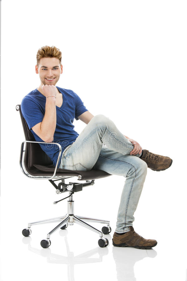 Young man sitting on a chair. Good looking young man sitting on a chair, isolated on white background stock photos