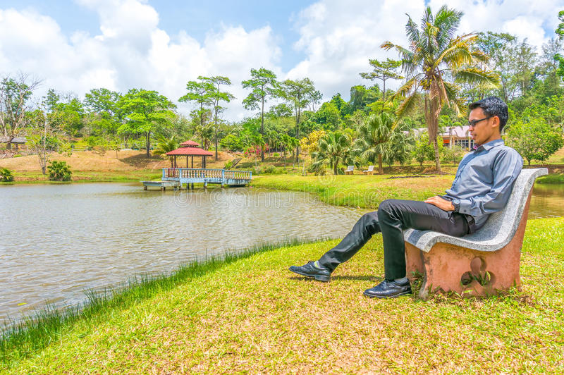 Download A Young Man Sitting On The Chair Stock Photo - Image of lake, male: 39509540