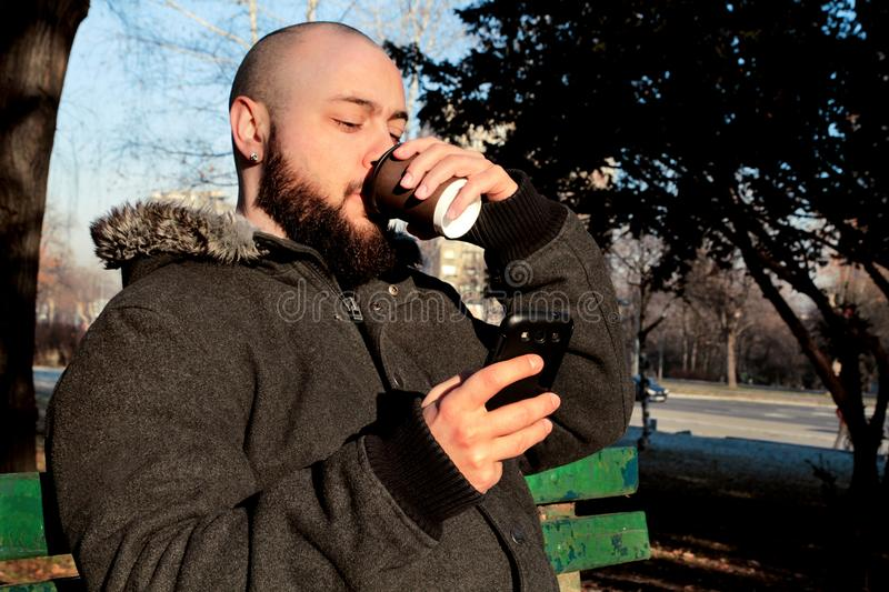 Man sitting in park with smartphone and drinking takeaway coffee royalty free stock photos