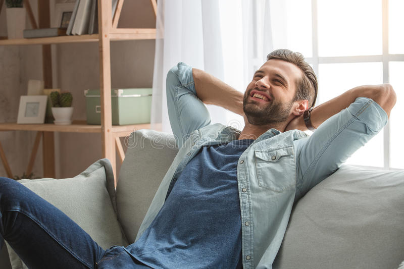 Young man sitting on coach rest at home stock image