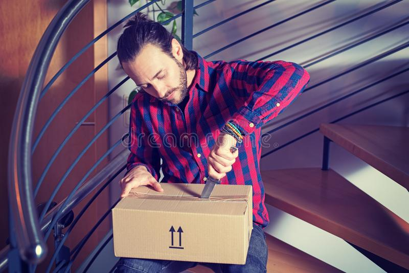 Man sitting in corridor and opening a package stock photo