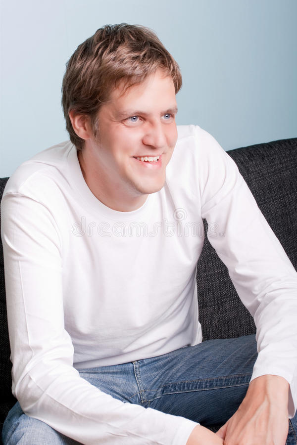Young man sitting on the couch stock images