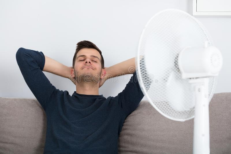Man Sitting On Couch Cooling Off With Fan royalty free stock photography
