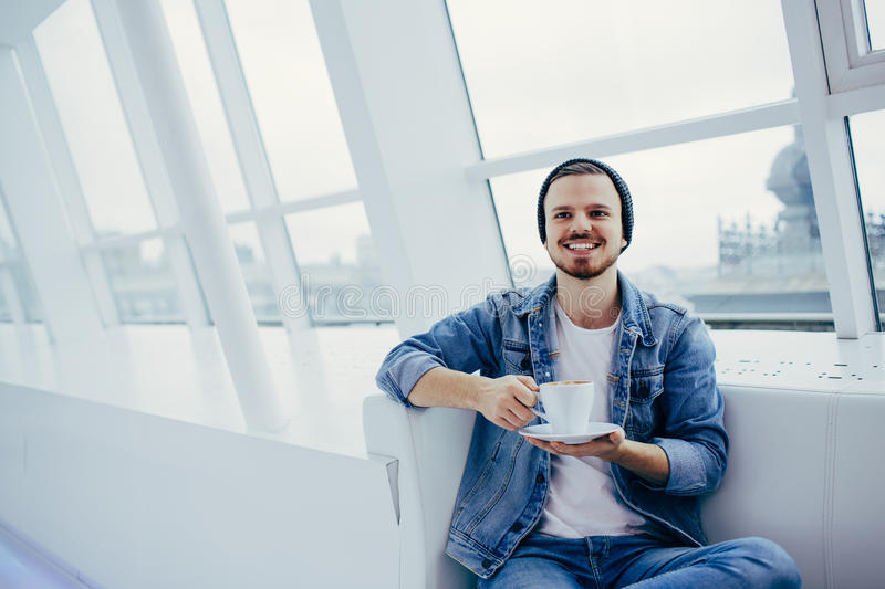 Young man sitting on the couch drinking a cup of coofee royalty free stock images