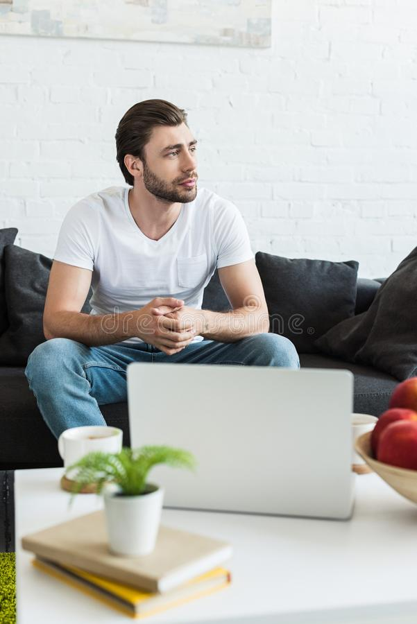 young man sitting on couch near table with coffee cups laptop books royalty free stock photography