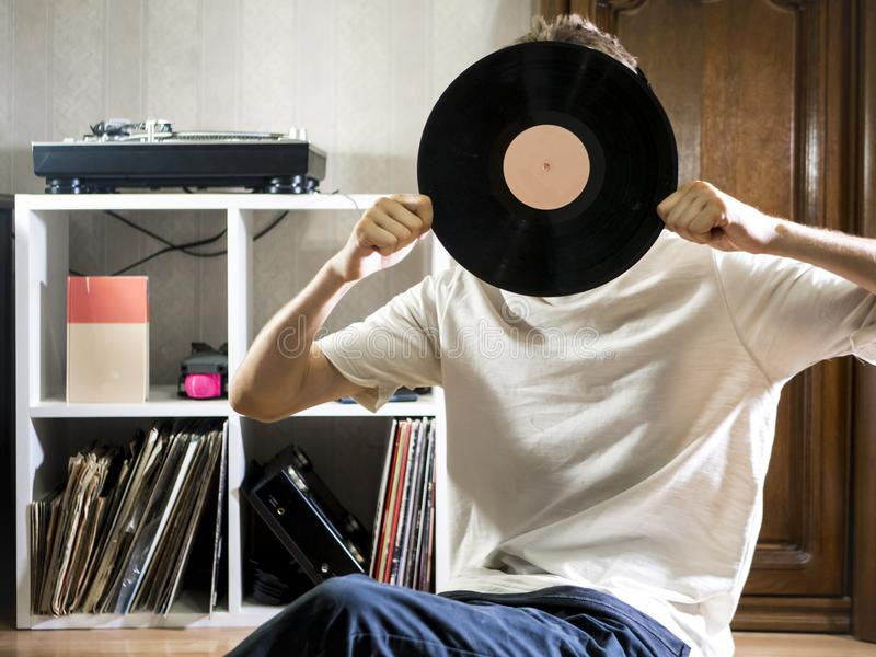 Young man sitting in cozy living room holding the vinyl record disk near records rack on the floor stock images